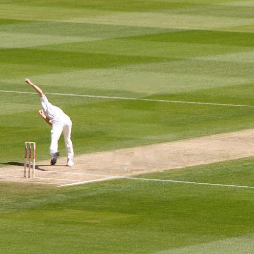 A fast bowler sends down a delivery as the batsman readys himself