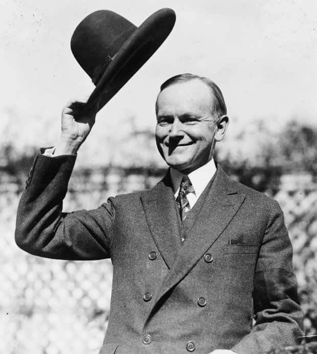 A courteous gentleman tipping his hat in a black and white era of yesteryear