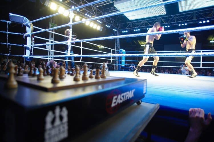 Chess board in foreground of a boxing match