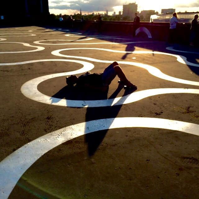 An image of a man lying on the floor as the sun creates a silhouette of his figure
