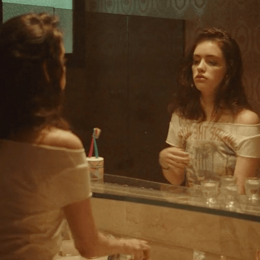 A girl staring at her reflection in the mirror