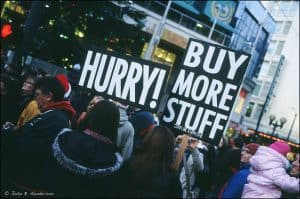 A group of protesters hold up boards with the words 'Hurry!' and 'Buy More Stuff' on them