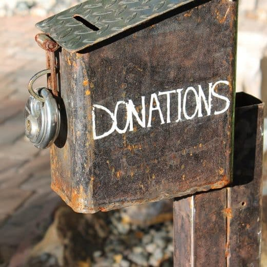 A rough rusty old donations box padlocked up.