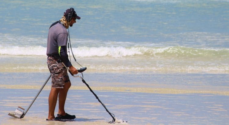 A man scouring the beach with a metal detector