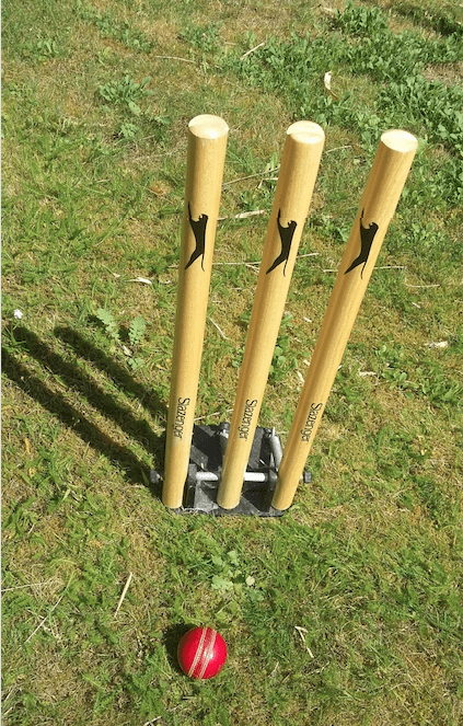 Cricket ball, green grass and stumps on a sunny day