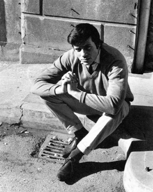 A young Oliver Reed sat on the curb of a street