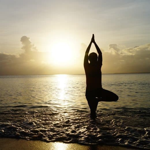 Someone doing a yoga pose on a beach in front of the water. They have their hands up and stand on one leg in a sun salutation position