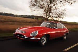 Red E Type Jaguar driving down a country road