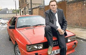 Gene Hunt from TV series Ashes To Ashes sits on the bonett of a red Audi Quattro