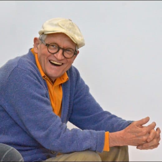 David Hockney sat in a chair with a white flat cap on with his hands claspt an leaning on his knees