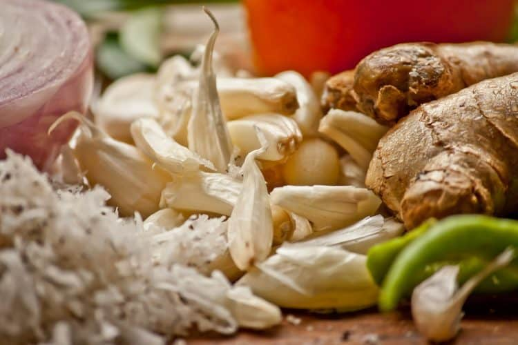 Picture of a table full of fresh produce including garlic, onion and ginger