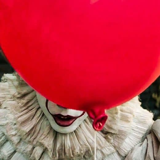 Picture of clown Pennywise from remake of IT. He is hiding behind red balloon so you can just see his mouth
