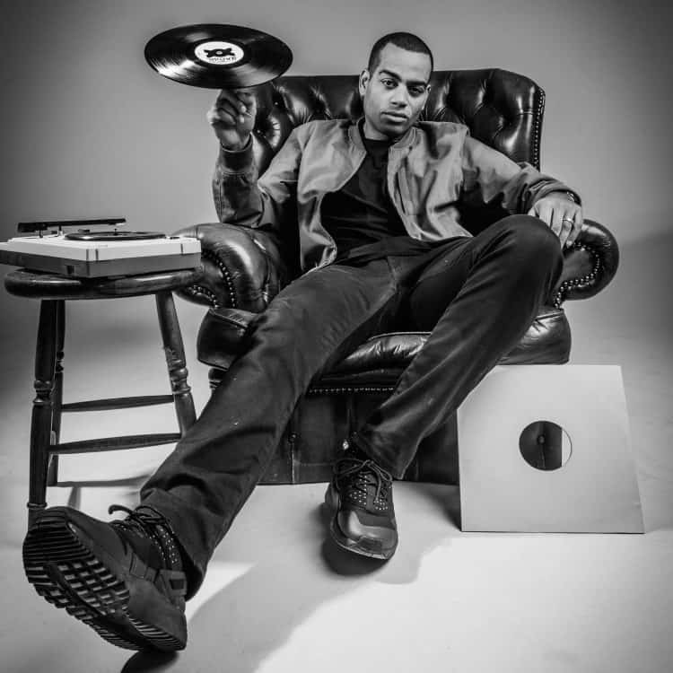 Comedian and rapper Doc Brown sits in a leather arm chair spinning a record on a finger of his right hand