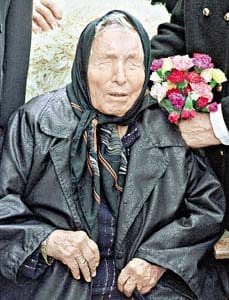 Late blind Balkan mystic Baba Vagna sits down in a dark coat with a bunch of flowers behind her