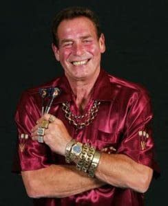 Darts player Bobby George smiles into the camera wearing a shiny red shirt and holding three darts. His arms are crossed into his chest