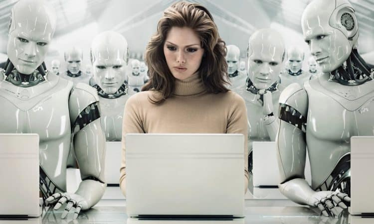 A women working on a laptop sits in a room full of human looking robots made out of shiny plastic