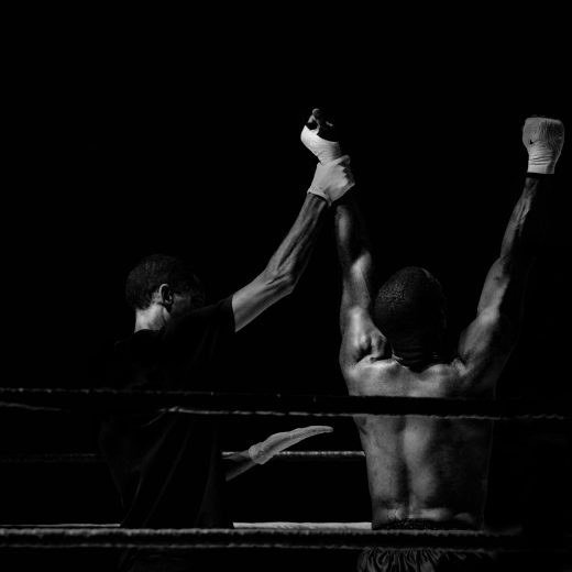 Two boxers at the end of the fight as the winner is announced - black and white