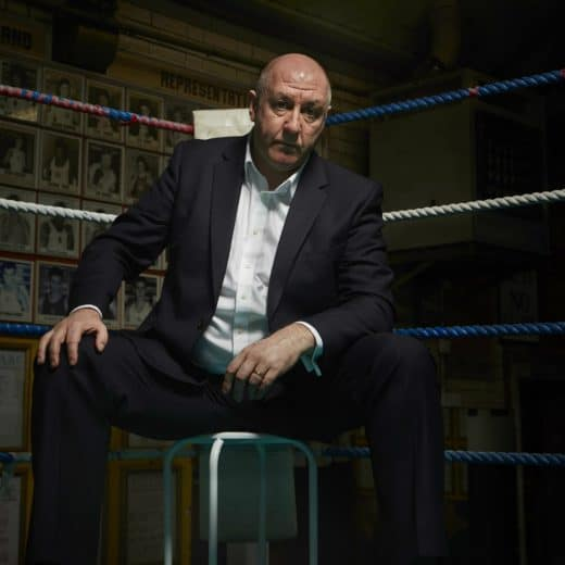 Steve Bunce sits in the corner of a boxing ring on a stool looking moodily into camera like a gangster