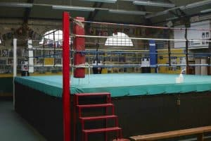 A boxing ring in a london boxing gym. It has green canvas with red steps leading up to it. It has three multi-coloured ropes