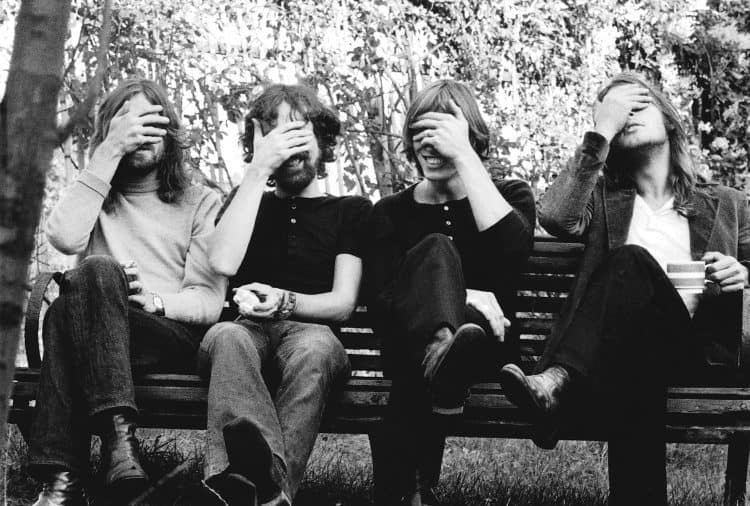 The band Pink Flord sit on a bench in a 70s black and white picture with their hands over their eyes