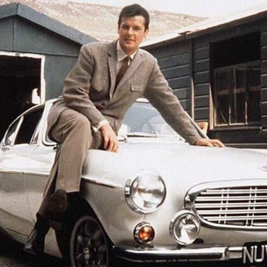 Roger Moore on bonnet of silver car