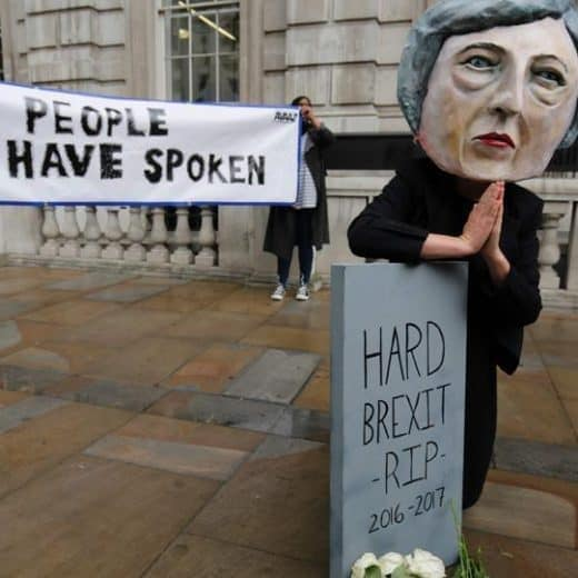 A masked person pretending to be Theresa May leans over a model gravestone that reads 'R.I.P. Hard Brexit'. Pick is in Peter Spencer's State of the Nation feature