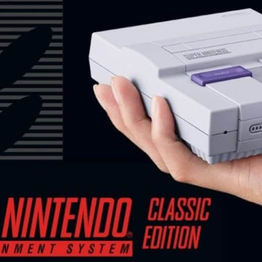 Mini Nintendo SNES classic held in the palm of someones hand