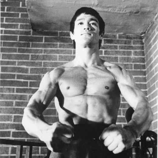 Bruce Lee black and white photo. He stands with hisfists in front of him with ripped torso on display