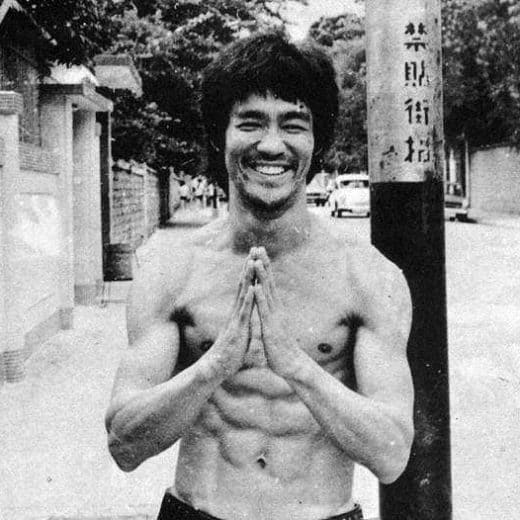 A shirtless Bruce Lee stands shirtless on a street corner, smiling with his hands clasped together