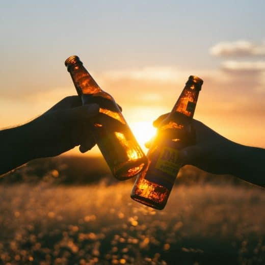 Hands 'Cheers' beer bottles together