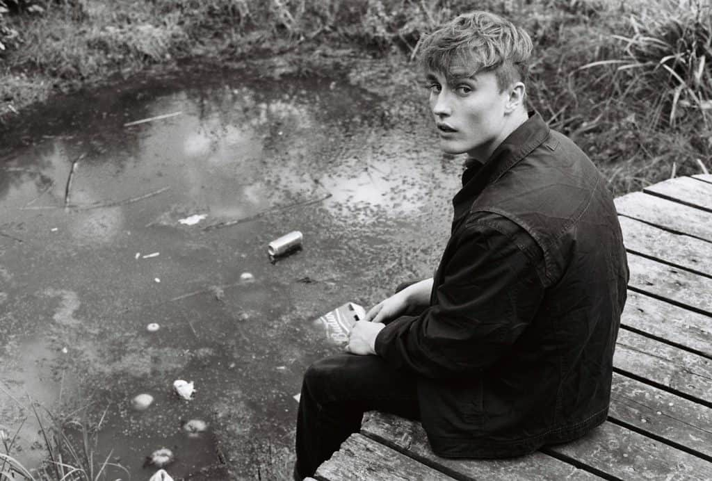 Sam Fender sat on a bridge