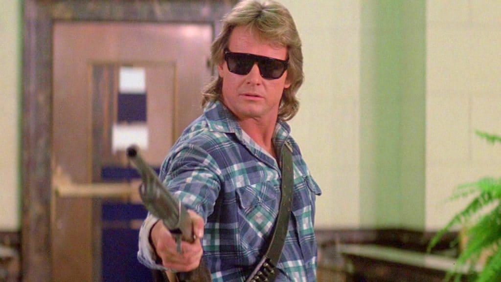 John Nada in sunglasses holding a shotgun