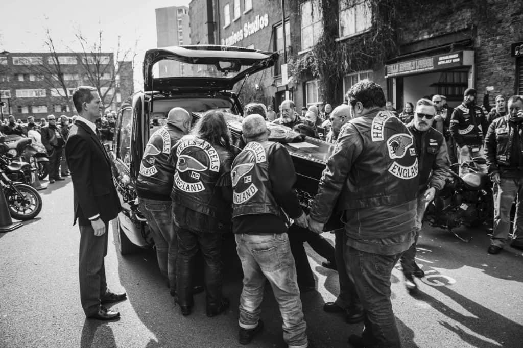 Hell's Angels members loading a coffin into a hearse