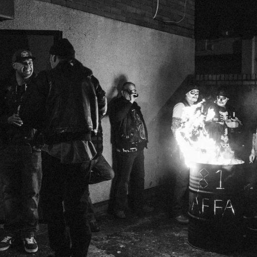 Hell's Angels members standing around a fire in a barrel