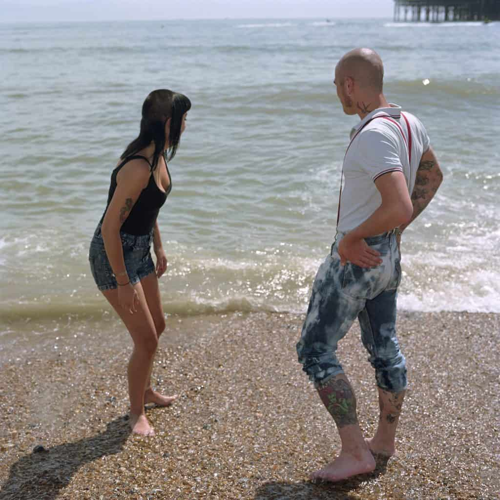 Two skinheads paddle on Brighton beach