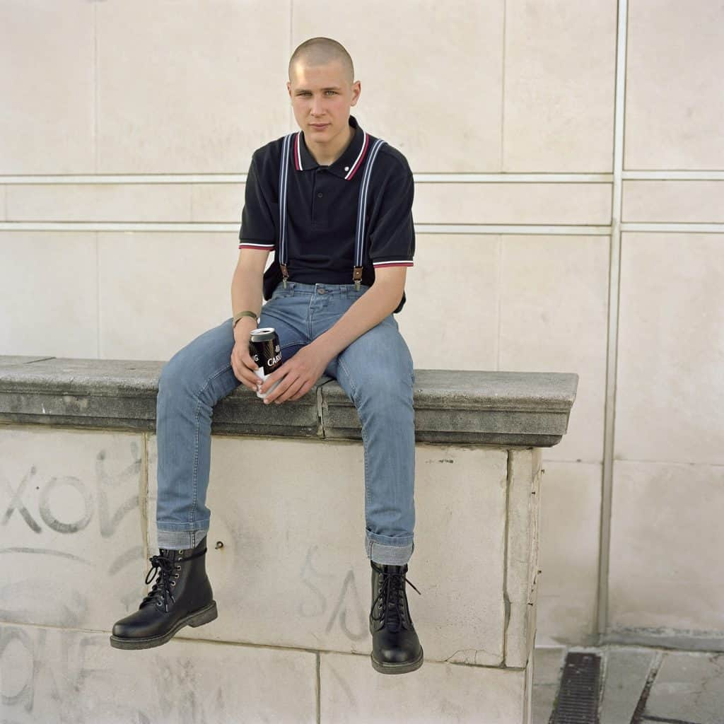 A skinhead sat on a wall with a can of Carling beer