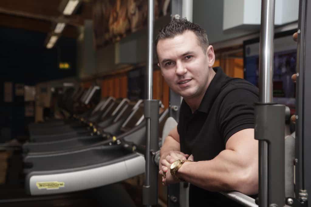 Matt Fiddes in the gym leaning on a weights machine