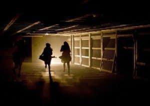 Two women walking in a shadowy corridor
