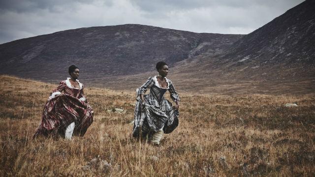 Two women in period dresses run across a mountain range