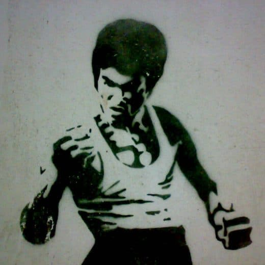 A black and white wall stencil of Bruce Lee in a fighting stance