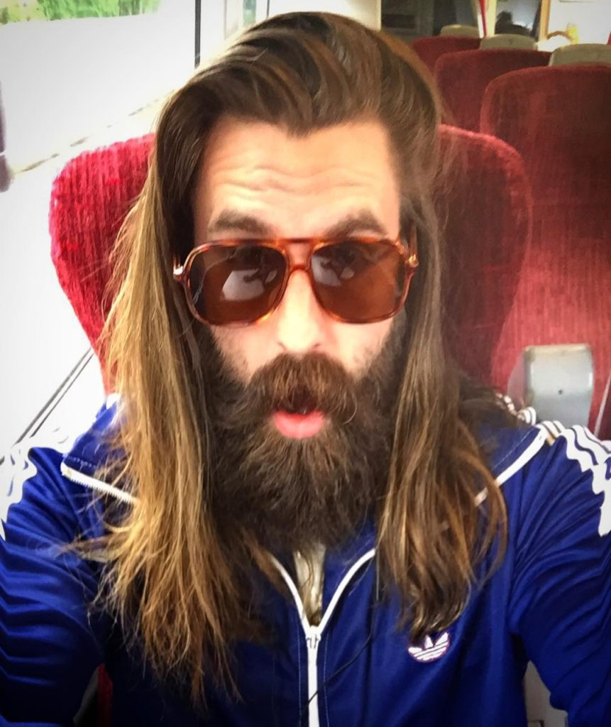 Ricki Hall takes a selfie of himself on a train. He wears a blue zip up Adidas top and brown tortoise shell shades. He has long brown hair and a bushy beard
