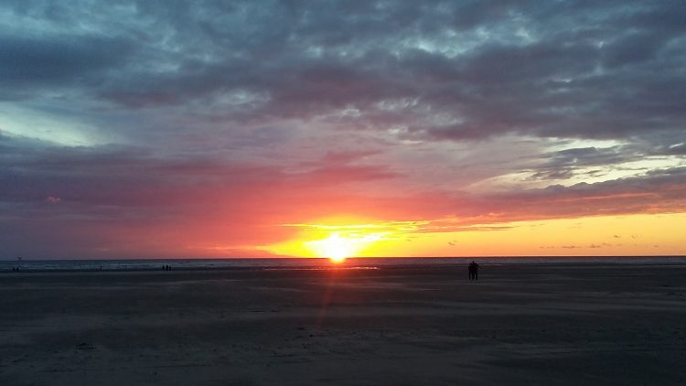 Picture of a sunset on Ainsdale beach. The sky is glowing below deep blue clouds