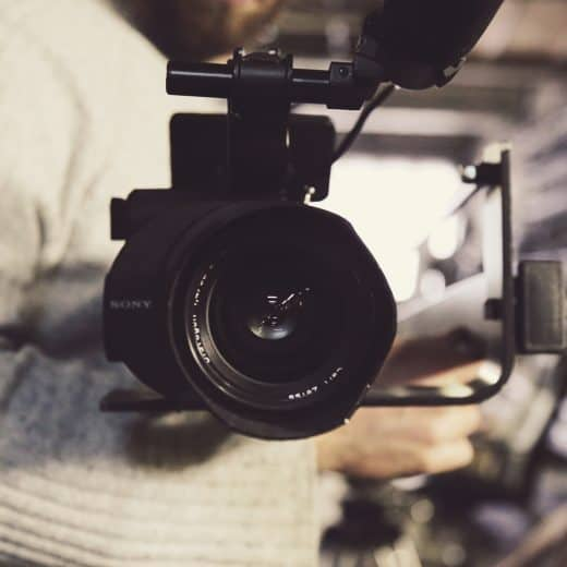 A close up image of a film camera being held by a cameraman