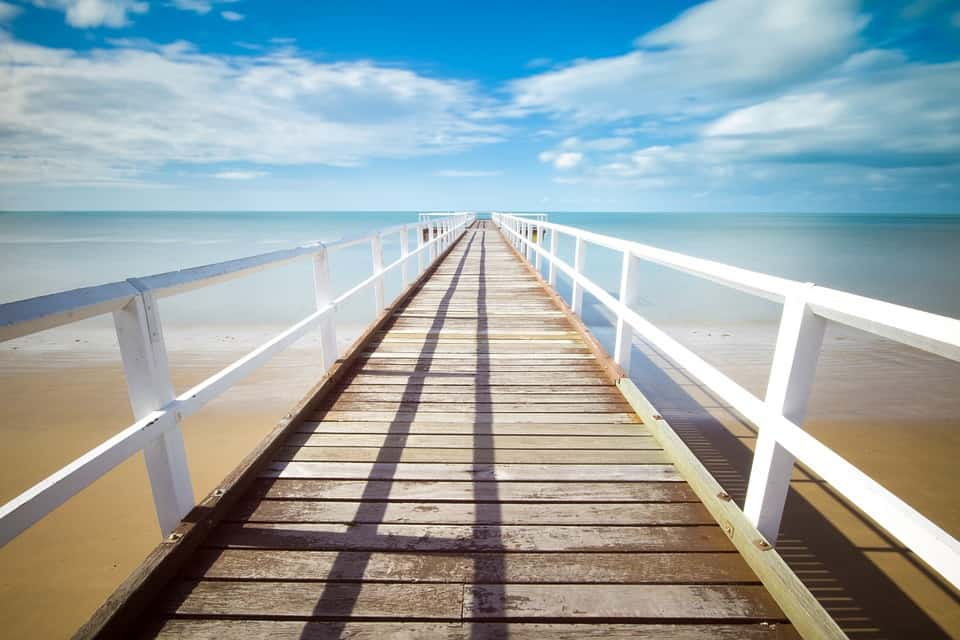 An image of a wooden jetty on a pristine clear blue sea