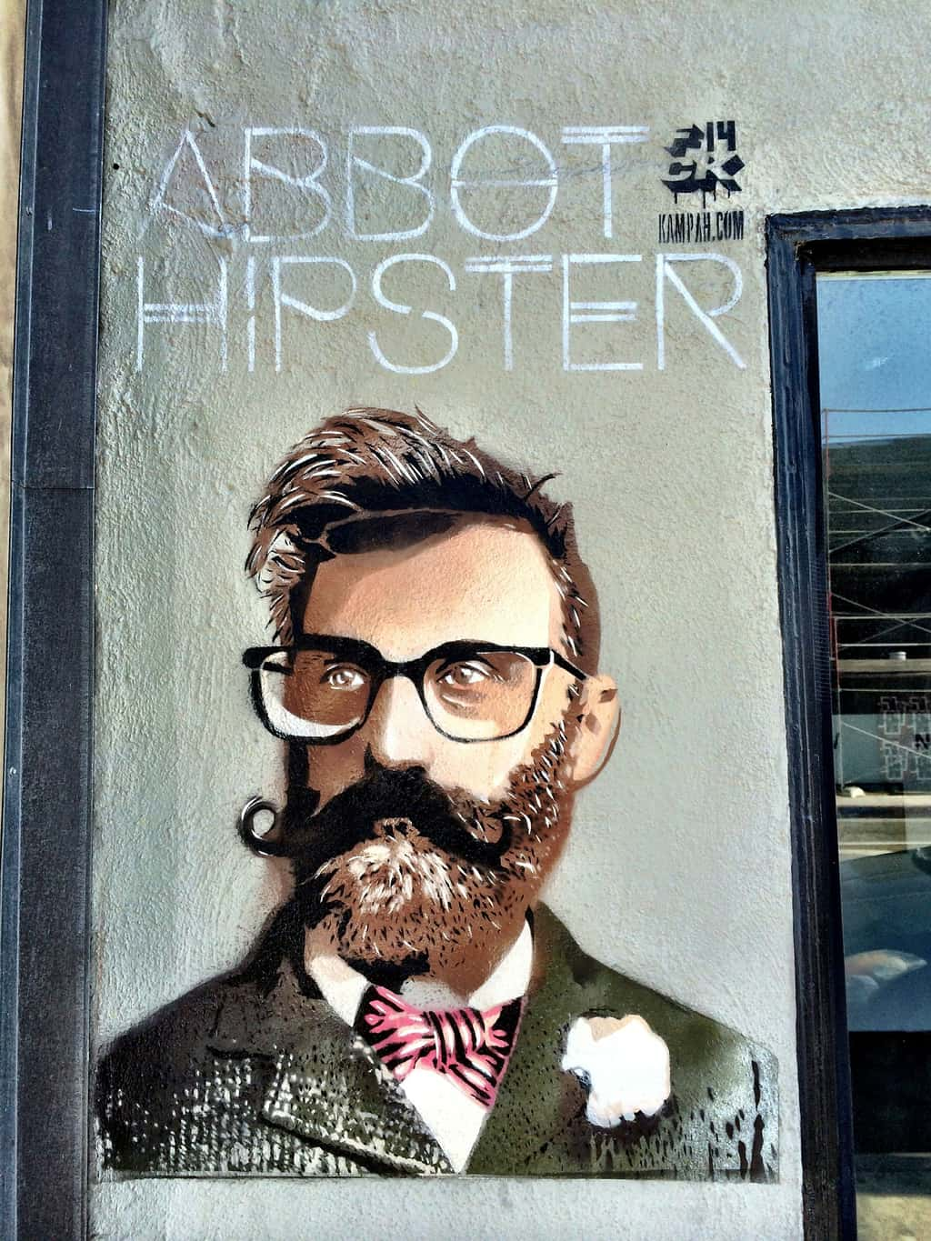 Graffiti picture of a hipster on a grey wall. The hipster has a quiff, glasses and a beard and twirled moustache. He wears a tweed suit with a bowtie