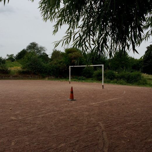 A traffic cone looks stark in front of a dusty football goal surrounded by trees