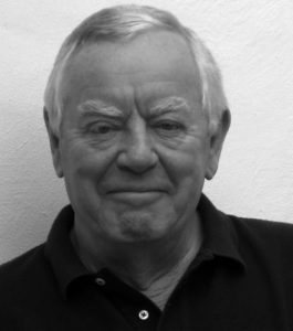 A black and white photo of Michael Deeley