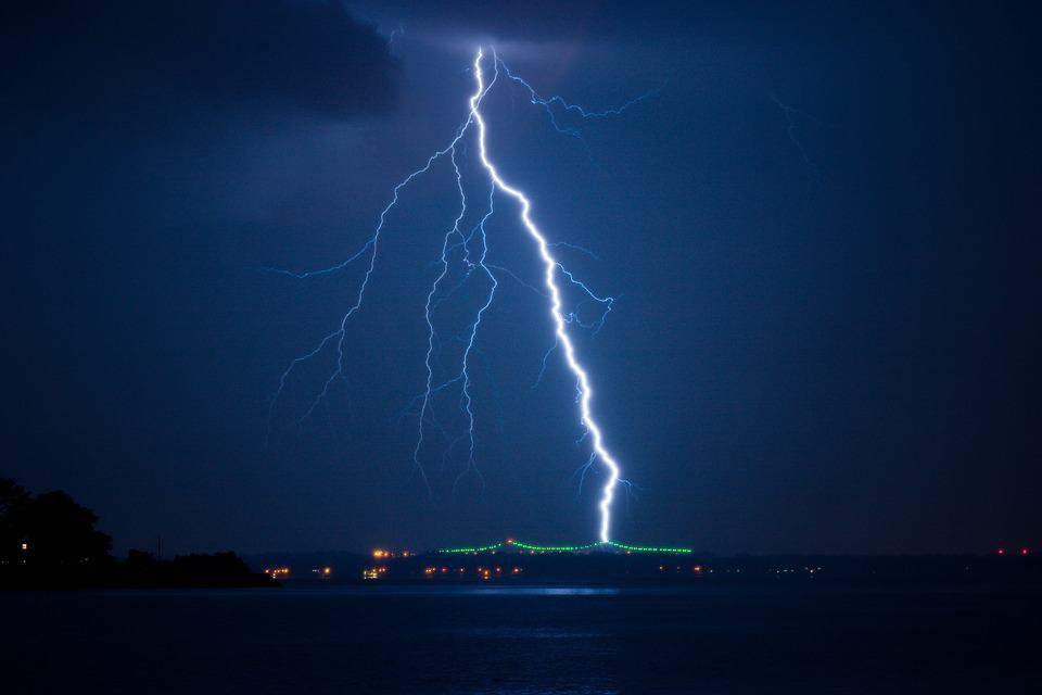 Lightning strikes over a dark blue town. Is it Rio?