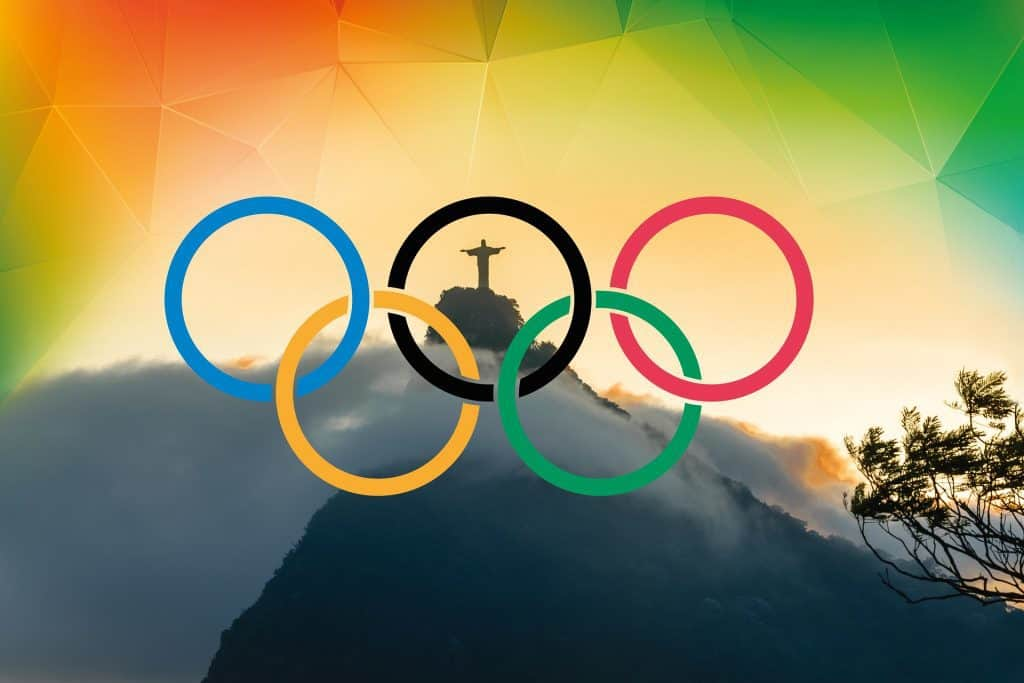 5 coloured Olympic rings with The Christ statue in Rio visible through them