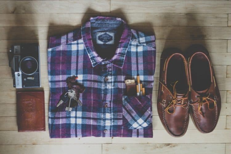A neatly folded and organsied set of shirt shoes wallet camera keys ciggies and lighter!